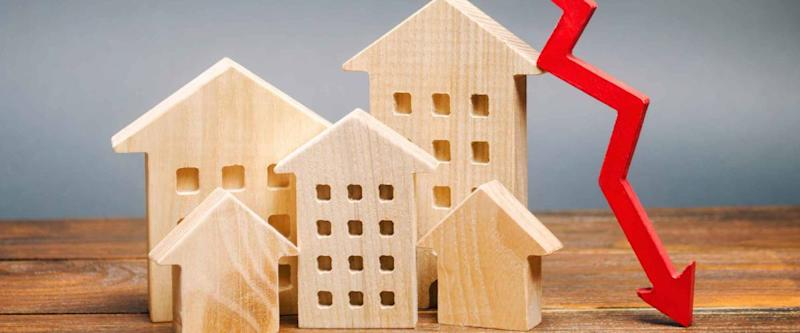 Miniature wooden houses and a red arrow down. The concept of falling mortgage rates