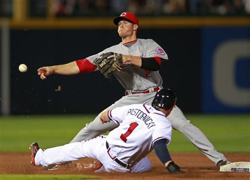 Cincinnati Reds shortstop Zack Cozart (2) forces out Atlanta Braves' Tyler Pastornicky (1) on a hit by Eric Hinske in the seventh inning of a baseball game, Monday, May 14, 2012, in Atlanta. (AP Photo/John Bazemore)