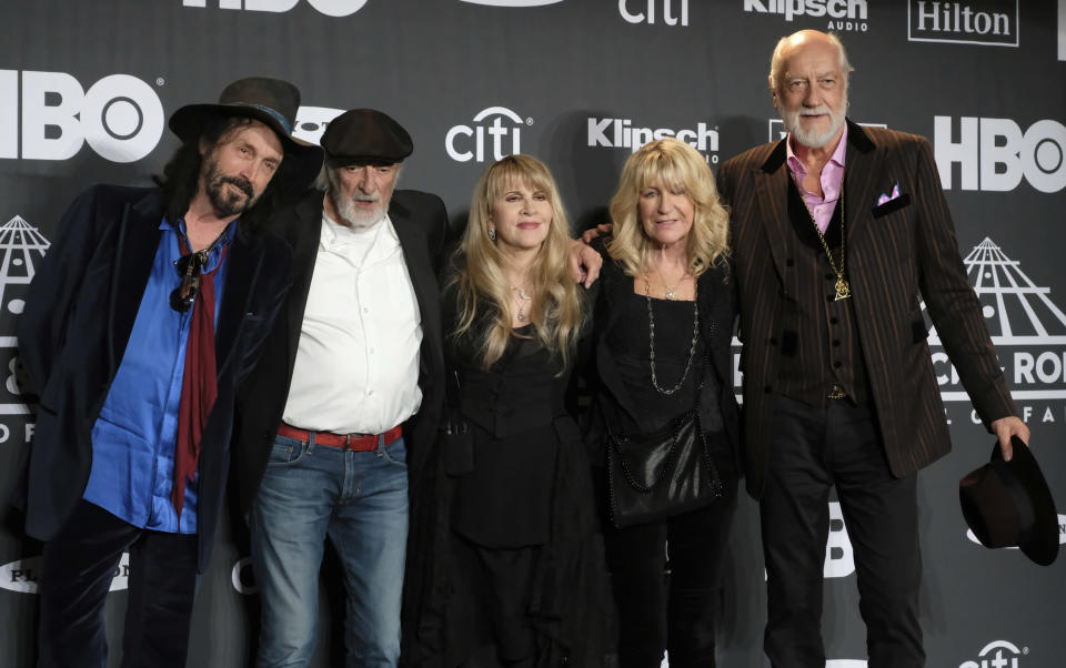 """FILE - This March 29, 2019 file photo shows Inductee Stevie Nicks, center, posing with other members of Fleetwood Mac, from left, Mike Campbell, John McVie, Christine McVie and Mick Fleetwood at the Rock & Roll Hall of Fame induction ceremony in New York. Nicks has spent the last 10 months homebound, mainly due to the coronavirus pandemic. During that time, she recorded the new single """"Show Them the Way,"""" releasing Friday and edited her new concert film """"Stevie Nicks 24 Karat Gold The Concert,"""" available at select theaters and drive-ins on Oct. 21 and 25. (Photo by Charles Sykes/Invision/AP, File)"""