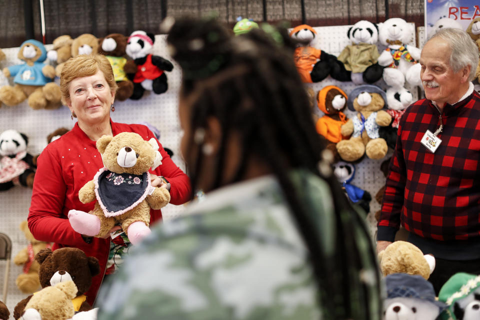 Workers help parents browse tables of donated holiday toys and stuffed animals at the Salvation Army Toy Shop, Tuesday, Dec. 11, 2018, in Cincinnati. (AP Photo/John Minchillo)
