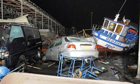 Vehicles and boats lie on the shore after a tsunami hit the northern port of Iquique