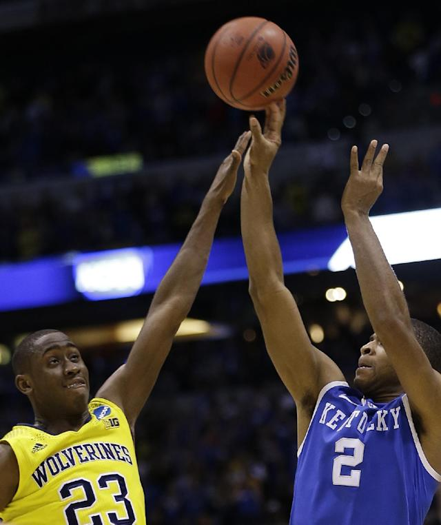 Kentucky's Aaron Harrison (2) shoots a three-point basket past Michigan's Caris LeVert (23) in the final second of the second half of an NCAA Midwest Regional final college basketball tournament game Sunday, March 30, 2014, in Indianapolis. (AP Photo/David J. Phillip)