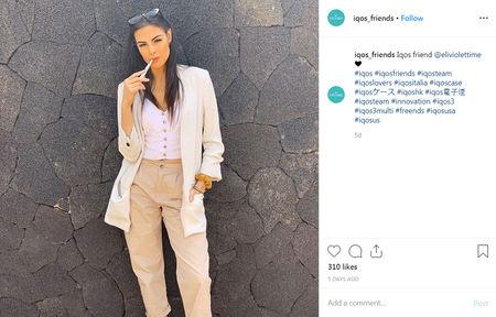 "Elicena Andrada, a model from Spain whose biography lists she was crowned Miss America Latino Del Mundo in 2017, holds an IQOS ""heated toballo"" device, made by Philip Morris International in an Instagram post on an account called @iqos_friends, in a post from May 12, 2019.       @iqos_friends/Social Media via REUTERS"