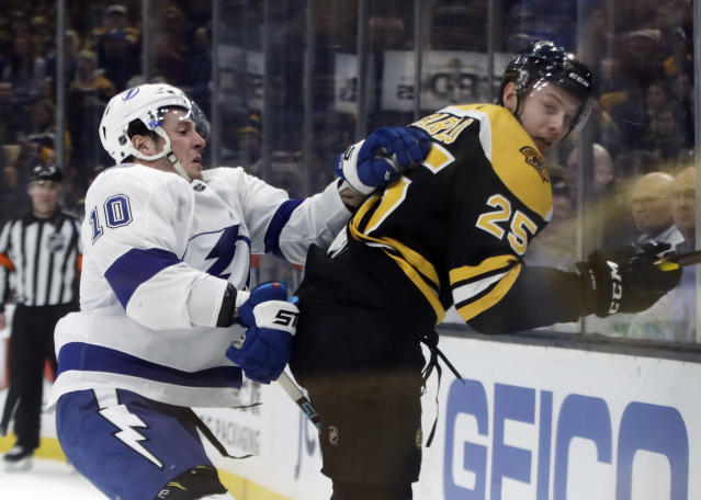 Tampa Bay Lightning center J.T. Miller (10) and Boston Bruins defenseman Brandon Carlo (25) compete along the boards in the first period of an NHL hockey game, Thursday, Feb. 28, 2019, in Boston. (AP Photo/Elise Amendola)
