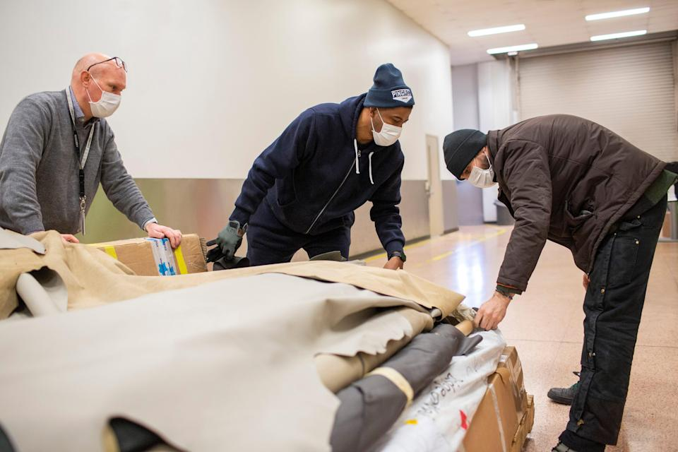 Left to right: Jim Conner, Ford 3D process director, is helping Nathaniel Crawford II and Jarret Schlaff, co-owners of Pingree Detroit, prepare to transport thousands of dollars in donated leather hides.