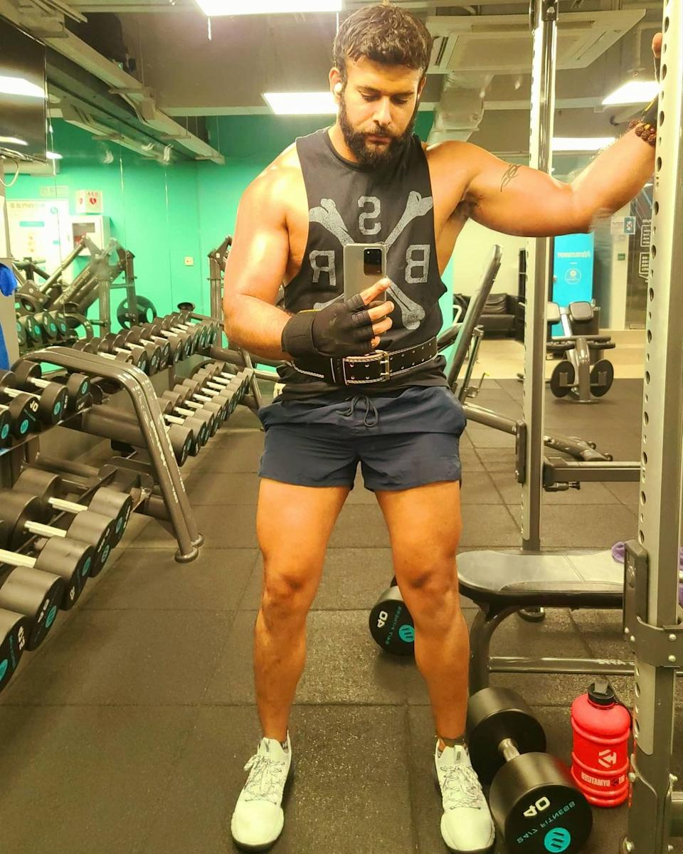 Dino Hira standing up showing off his muscles in the gym