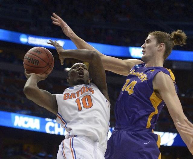Albany center John Puk (44) fouls Florida forward Dorian Finney-Smith (10) during the first half of a second-round game in the NCAA college basketball tournament on Thursday, March 20, 2014, in Orlando, Fla. (AP Photo/Phelan M. Ebenhack)