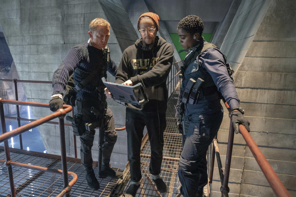 """This mage released by MGM shows director Cary Joji Fukunaga, center, with actors Daniel Craig, left, and Lashana Lynch on the set of the James Bond film """"No Time to Die."""" (Nicola Dove/MGM via AP)"""
