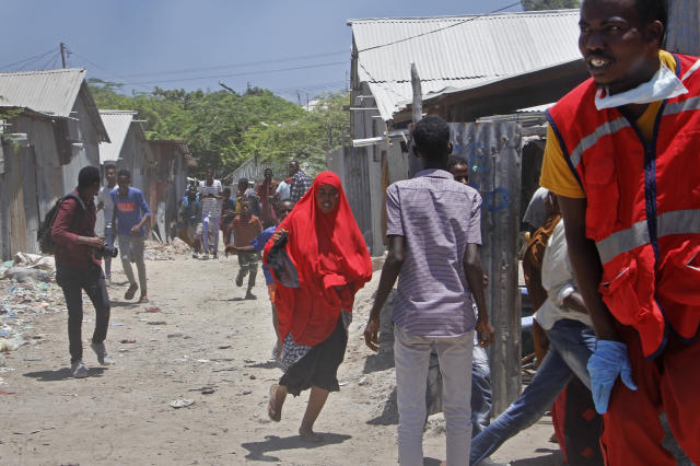 Somali civilians and medical workers run for cover from gunfire during ongoing fighting between government soldiers and gunmen after a suicide car bomb attack on a government building in the capital Mogadishu, Somalia Saturday, March 23, 2019. Al-Shabab gunmen stormed into the government building following a suicide car bombing at the gates on Saturday, a police officer said, in the latest attack by Islamic extremist fighters in the Horn of Africa nation. (AP Photo/Farah Abdi Warsameh)
