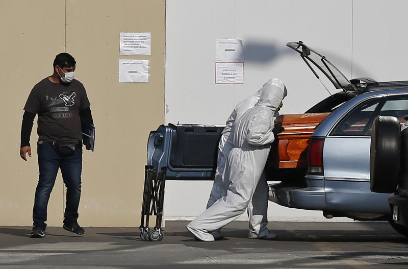 Employees of a funeral parlour put the coffin containing the body of a person who died of COVID-19 in the vehicle of a relative, outside the San Jose Hospital in Santiago, on June 1, 2020 amid the novel coronavirus pandemic. - Chile's economy nose-dived more than 14 percent in April compared to the same month in 2019 as the impact of the coronavirus lockdown took effect, the country's central bank said on Monday. Chile has recorded almost 100,000 COVID-19 cases and 1,000 deaths. (Photo by JAVIER TORRES / AFP) (Photo by JAVIER TORRES/AFP via Getty Images)