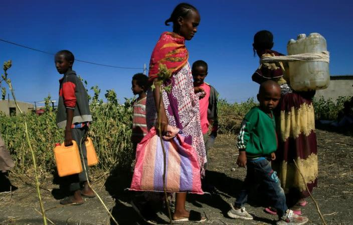Ethiopian refugees fleeing from the ongoing fighting in Tigray region, carry water jerrycans at the Fashaga camp, on the Sudan-Ethiopia border, in Kassala state