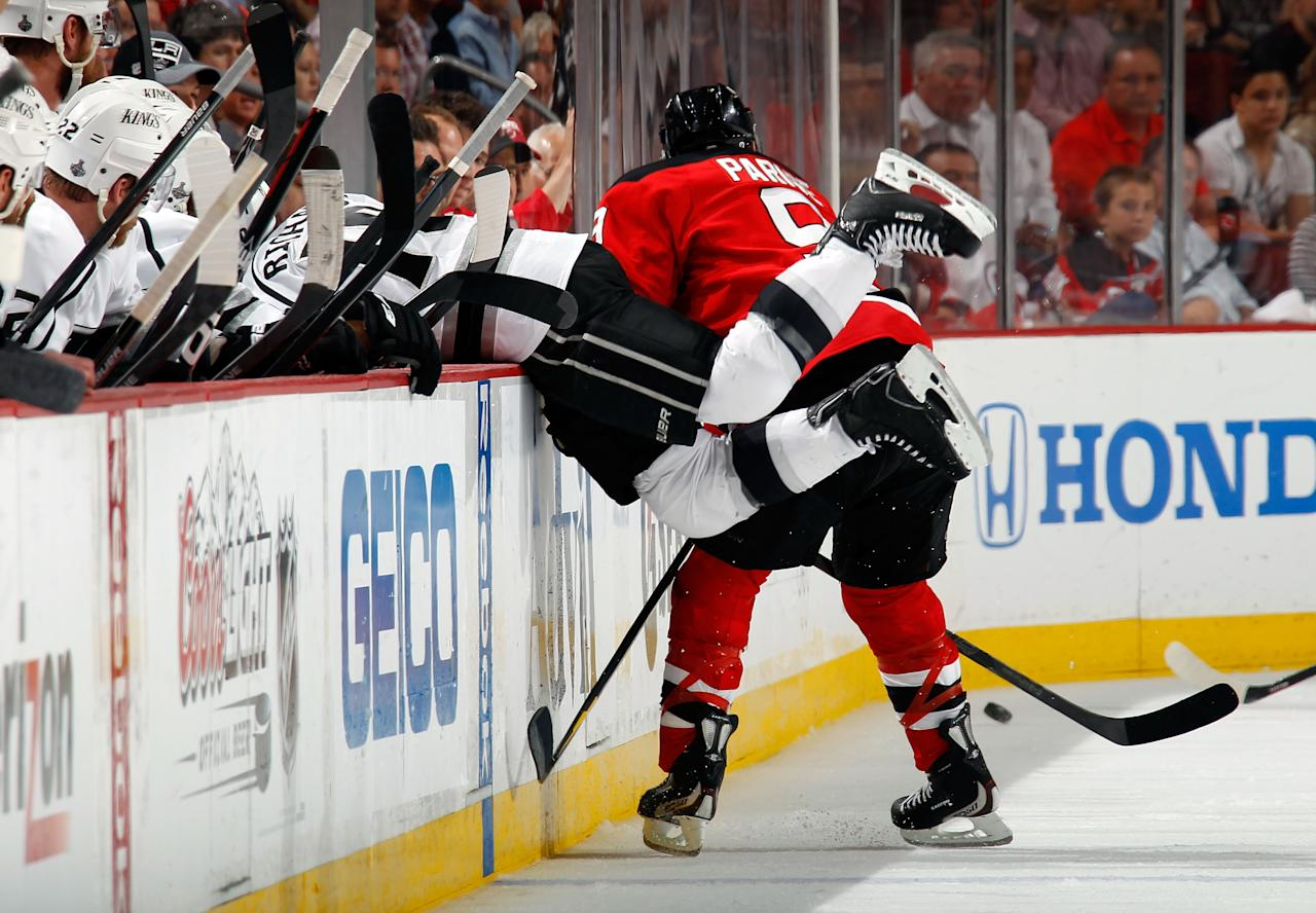 NEWARK, NJ - JUNE 09: Mike Richards #10 of the Los Angeles Kings falls into the bench as Zach Parise #9 of the New Jersey Devils makes contact during Game Five of the 2012 NHL Stanley Cup Final at the Prudential Center on June 9, 2012 in Newark, New Jersey.  (Photo by Bruce Bennett/Getty Images)