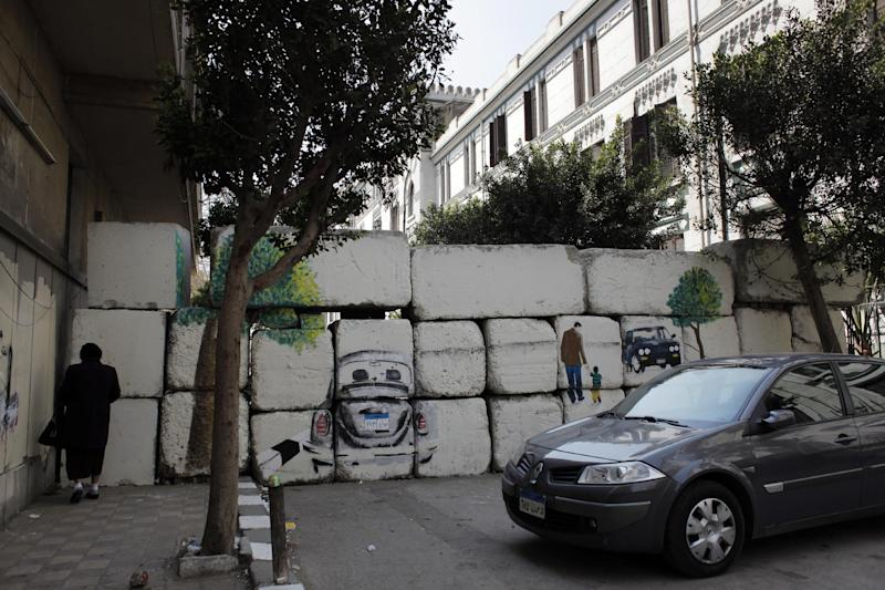 In this Wednesday, March 21, 2012 photo, an Egyptian woman walks toward the painted concrete blocks wall that was part of the graffiti campaign to paint a reproduction of the streets behind them and targeted the concrete blocks walls in downtown Cairo, Egypt. After Egypt's ruling military sealed off streets around Cairo's Tahrir Square with walls of imposing concrete blocks, a group of artists decided to reopen the avenues on their own, in the public imagination, at least. (AP Photo/Nasser Nasser)