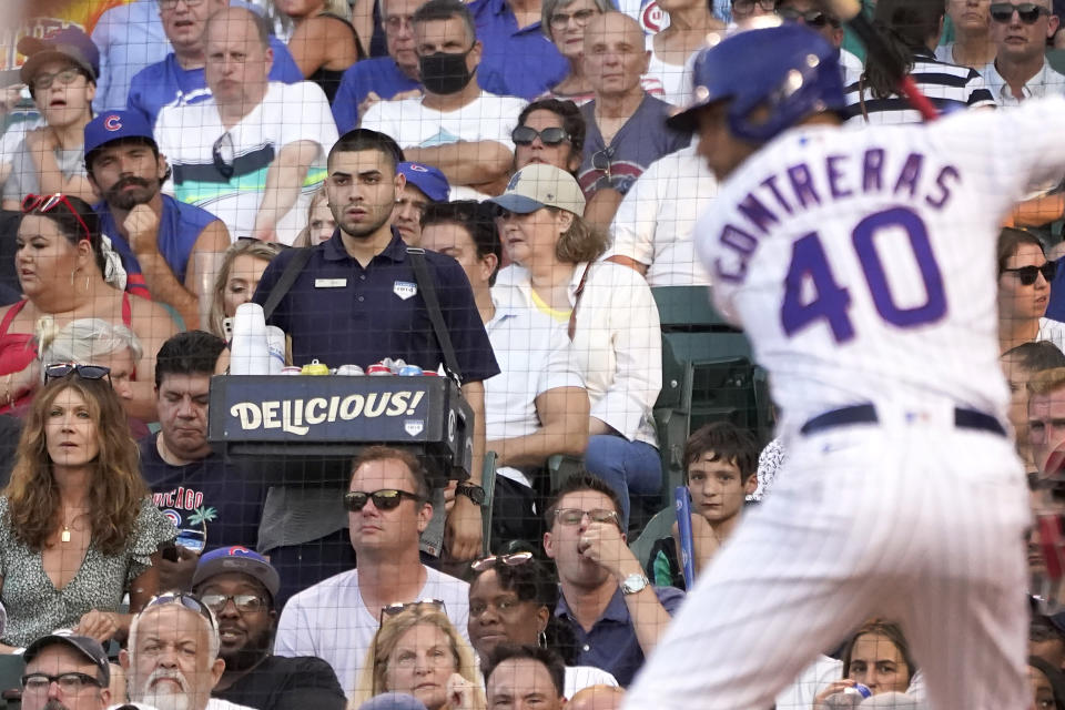 A concessions worker walks the aisle near home plate as Chicago Cubs' Willson Contreras waits for a pitch during the second inning of a baseball game against the Philadelphia Phillies Monday, July 5, 2021, in Chicago. A majority of teams have now opened their parks to full capacity, and the rest are scheduled to do so soon. That could mean more good news for ballpark workers. (AP Photo/Charles Rex Arbogast)