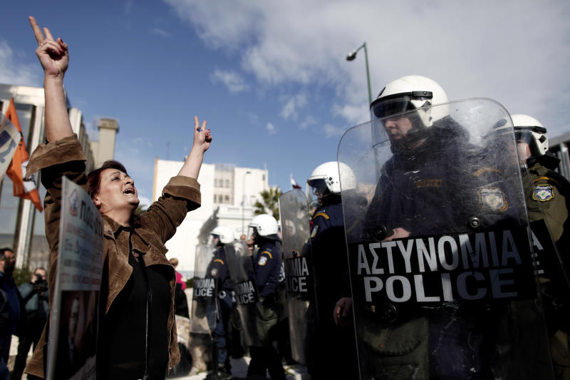 A Greek municipal employee shouts anti-government slogans as riot police look on, after a group of protesters pushed into the grounds of Parliament in Athens Wednesday, Dec. 12, 2012. Riot police prevented the protesters from advancing much further, and there were no clashes or arrests. Municipal employees are angry at government plans to include them on a list of state employees up for forced redundancy under the country's austerity program. (AP Photo/Petros Giannakouris)