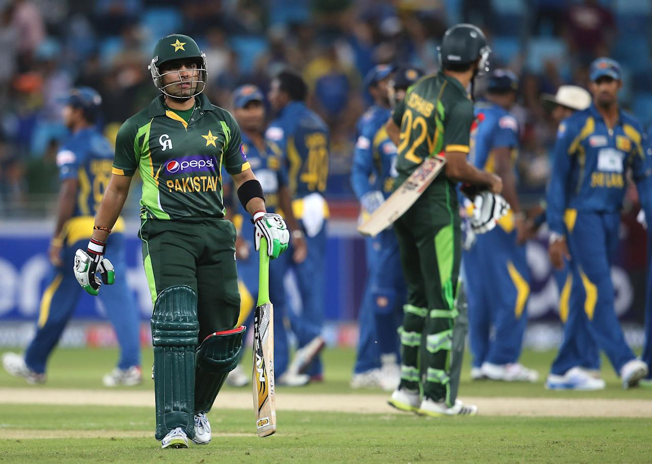 DUBAI, UNITED ARAB EMIRATES - DECEMBER 11:  Umar Akmal of Pakistan walks of the field after being dismissed during the first Twenty20 International match between Pakistan and Sri Lanka at Dubai Sports City Cricket Stadium on December 11, 2013 in Dubai, United Arab Emirates.  (Photo by Francois Nel/Getty Images)