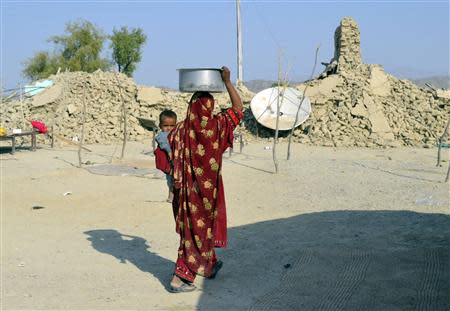A survivor of an earthquake carries a pot on her head filled with drinking water as she walks near the rubble of a mud house after it collapsed following the quake at Dhallbedi Peernder village in Awaran district