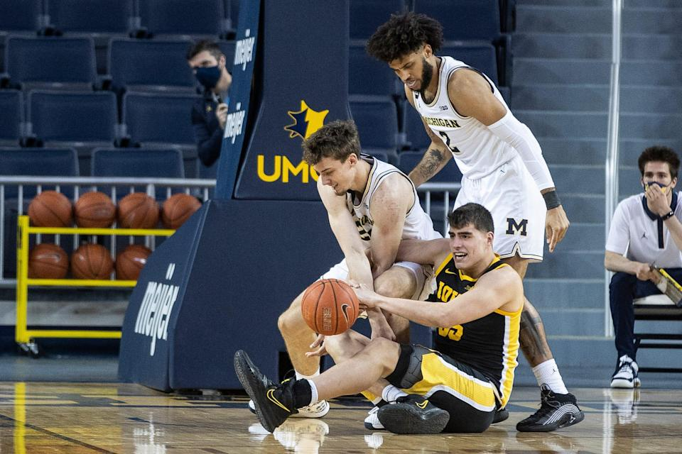 Michigan guard Franz Wagner and Iowa center Luka Garza battle for the loose ball during the first half at Crisler Center in Ann Arbor, Thursday, Feb. 25, 2021.