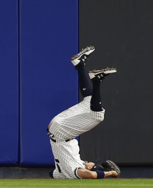 New York Yankees' Aaron Judge rolls after making a leaping catch of a ball hit by Houston Astros' Yuli Gurriel during the fourth inning of Game 3 of baseball's American League Championship Series Monday, Oct. 16, 2017, in New York. (AP Photo/Kathy Willens)