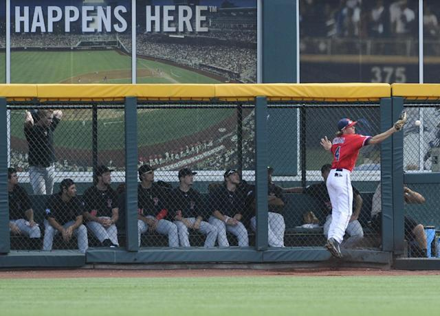 Texas Tech players in the bullpen watch as Mississippi right fielder Will Jamison (4) chases a ball hit by Texas Tech's Adam Kirsch for a triple in the sixth inning of an NCAA baseball College World Series elimination game in Omaha, Neb., Tuesday, June 17, 2014. (AP Photo/Eric Francis)