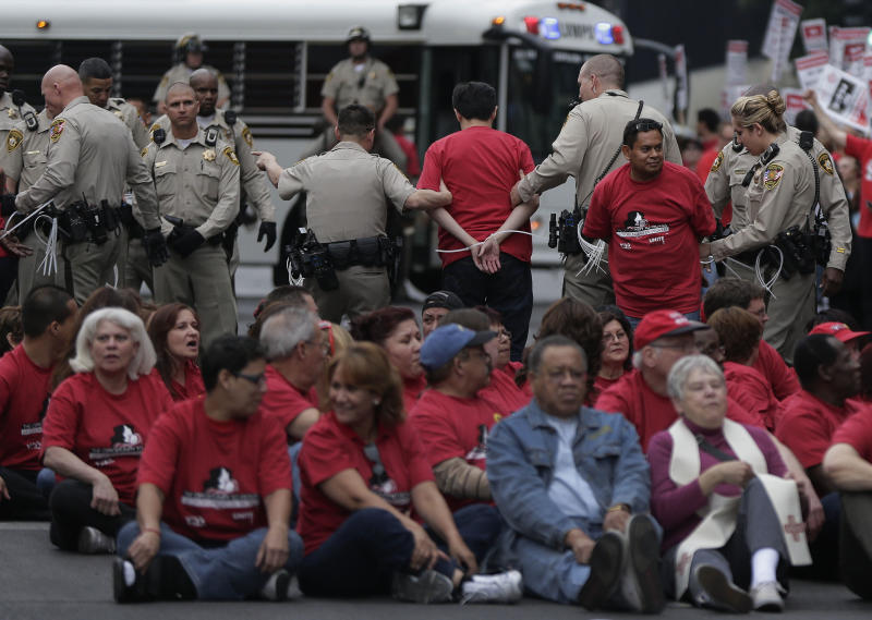 Las Vegas Metropolitan Police officers lead away a protestors during a civil disobedience demonstration by Culinary Union workers outside the Cosmopolitan Hotel-Casino, Wednesday, March 20, 2013, in Las Vegas. Nearly 98 protestors were arrested during the demonstration in which they sat on and blocked traffic along Las Vegas Boulevard. Workers have been in contract talks with Cosmopolitan Las Vegas owner Deutsche Bank for two years. (AP Photo/Julie Jacobson)
