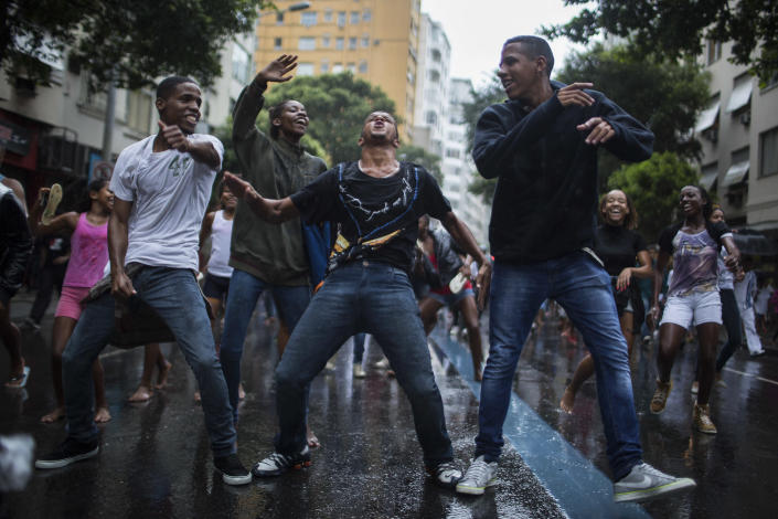Friends and Residents of Pavao-Pavaozinho slum dance during a protest in the streets of Copacabana against the death of Douglas Rafael da Silva Pereira, after his burial in Rio de Janeiro, Brazil, Thursday, April 24, 2014. The protest followed the burial Pereira, whose shooting death sparked clashes Tuesday night between police and residents of the Pavao-Pavaozinho slum. (AP Photo/Felipe Dana)
