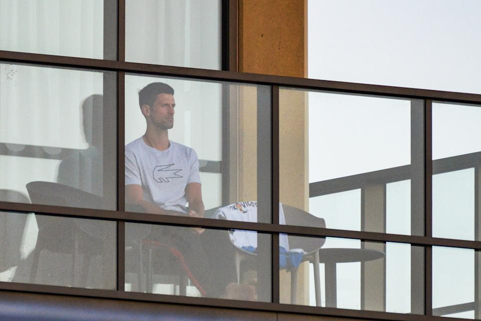 Men's singles world number one tennis player Novak Djokovic of Serbia sits on his hotel balcony in Adelaide on January 18, 2021, one of the locations where players have quarantined for two weeks upon their arrival ahead of the Australian Open tennis tournament in Melbourne. (Photo by Brenton EDWARDS / AFP) / -- IMAGE RESTRICTED TO EDITORIAL USE - STRICTLY NO COMMERCIAL USE -- (Photo by BRENTON EDWARDS/AFP via Getty Images)