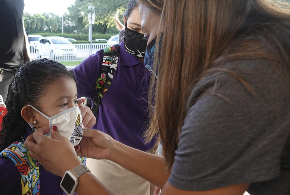 Dolphin Bay Elementary School kindergarten student Isabela Osorio gets an assist with her mask from her sister Valentina and Assistant Principal Janet Blano Soto, Wednesday, Aug. 16, 2021 in Miramar, Fla. More than 261,000 Broward County Public Schools (BCPS) students headed back to school to begin the 2021/22 school year. (Joe Cavaretta/South Florida Sun-Sentinel via AP)