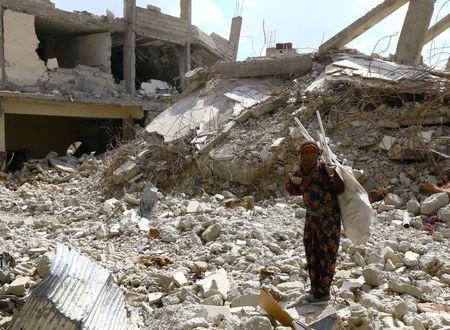 A woman gestures as she stands on rubble of damaged buildings in Raqqa