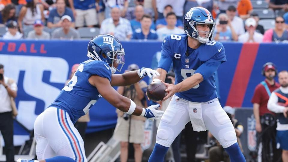 Sep 12, 2021; East Rutherford, New Jersey, USA; New York Giants quarterback Daniel Jones (8) hands off to running back Saquon Barkley (26) during the first quarter against the Denver Broncos at MetLife Stadium.