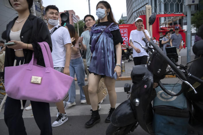 """People walk across an intersection during rush hour in Beijing, Friday, July 2, 2021. A small but visible handful of urban Chinese are rattling the ruling Communist Party by choosing to """"lie flat,"""" or reject high-status careers, long work hours and expensive cities for a """"low-desire life."""" That clashes with party ambitions to make China a wealthier consumer society. (AP Photo/Mark Schiefelbein)"""