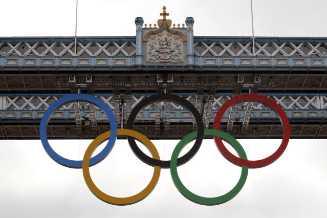 The Olympic rings are seen atop the iconic Tower Bridge in London, after they were lowered into position, coinciding with one month to go until the start of London 2012 Games, Wednesday, June 27, 2012. The giant rings, which are fully retractable to allow for tall ships to pass through the bridge, will remain in position for the duration of the Games. (AP Photo/Lefteris Pitarakis)