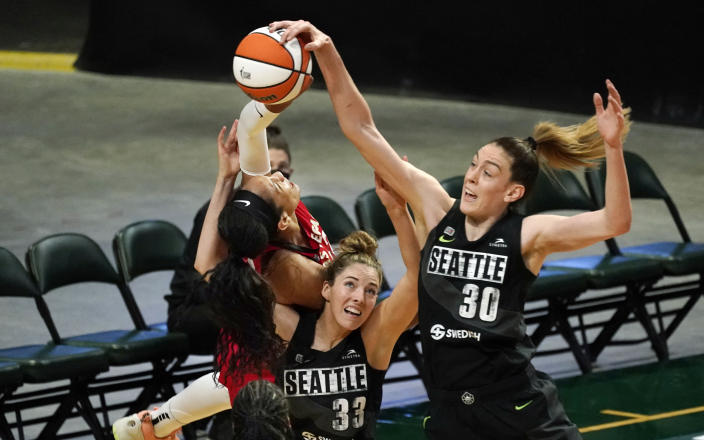 Seattle Storm's Katie Lou Samuelson (33) and Breanna Stewart (30) surround Las Vegas Aces' A'ja Wilson as they vie for the ball in the first half of a WNBA basketball game Saturday, May 15, 2021, in Everett, Wash. The Storm won 97-83. (AP Photo/Elaine Thompson)