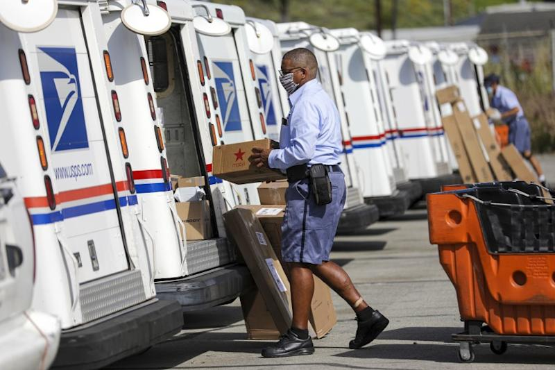 SAN CLEMENTE, CA - MAY 15: James Daniels, 59, a postal carrier, loads mail in his truck for delivery at San Clemente Post Office on Friday, May 15, 2020 in San Clemente, CA. (Irfan Khan / Los Angeles Times)