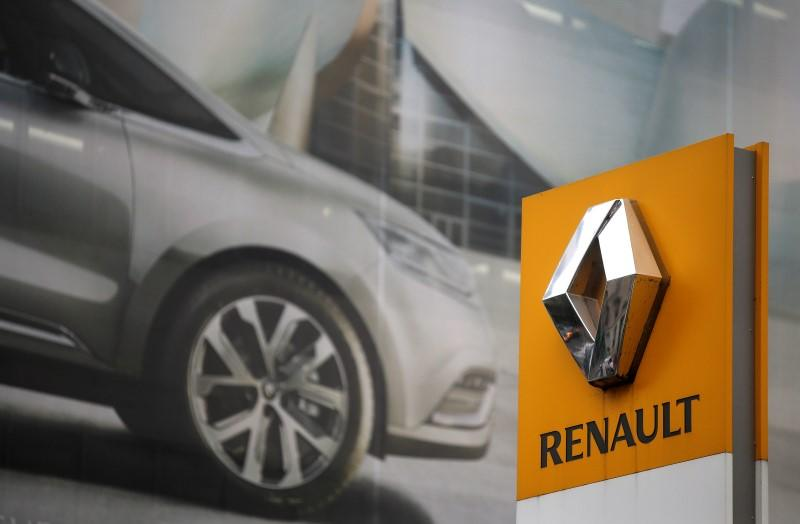 The logo of French car manufacturer Renault is seen in front of an advertisement at a dealership in Paris