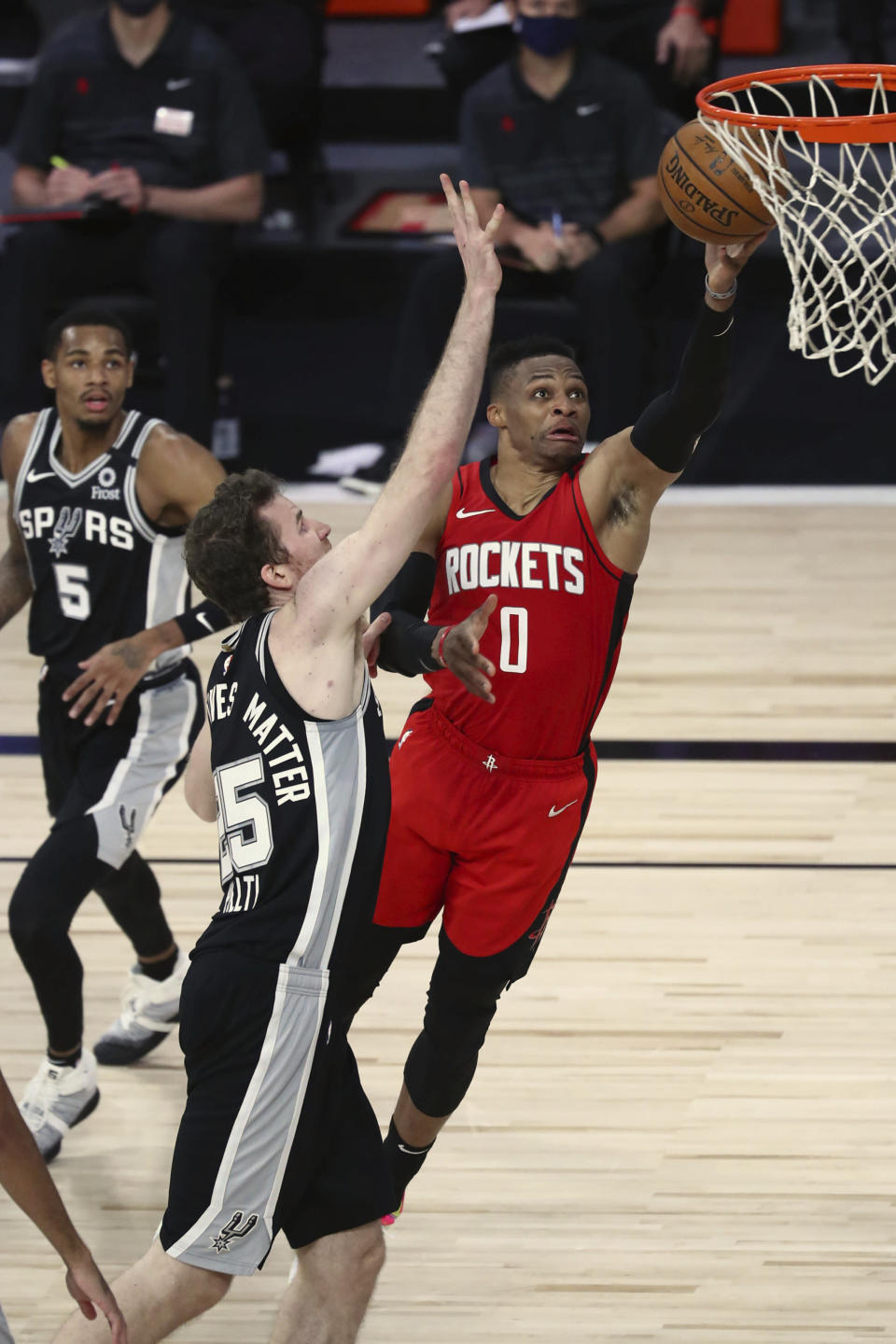 Houston Rockets guard Russell Westbrook (0) goes up for a shot past San Antonio Spurs center Jakob Poeltl (25) during the first half of an NBA basketball game Tuesday, Aug. 11, 2020, in Lake Buena Vista, Fla. (Kim Klement/Pool Photo via AP)