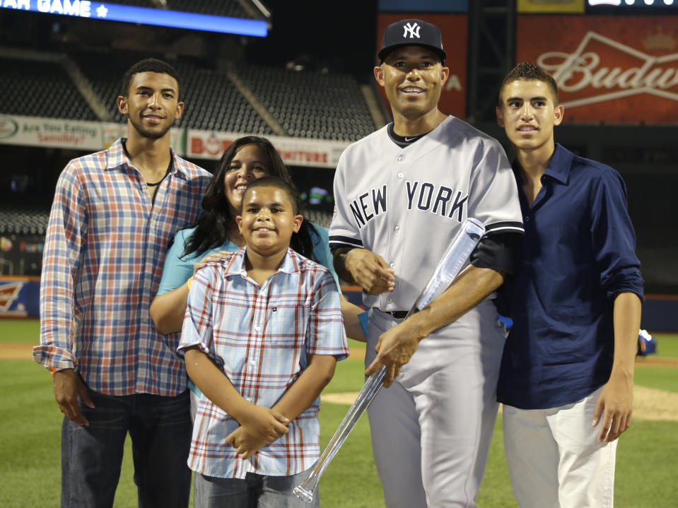 American League's Mariano Rivera, of the New York Yankees, poses with the MVP trophy and his family after the MLB All-Star baseball game, on Tuesday, July 16, 2013, in New York. The American League defeated the National League 3-0. (AP Photo/Matt Slocum)