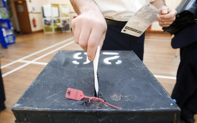 A voter places his voting card in the ballot box at a polling station in South London