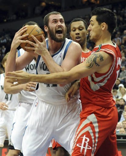 Minnesota Timberwolves' Kevin Love, left, reacts as Houston Rockets' Carlos Delfino, of Argentina, defends in the first half of an NBA basketball game, Wednesday, Dec. 26, 2012, in Minneapolis. (AP Photo/Jim Mone)