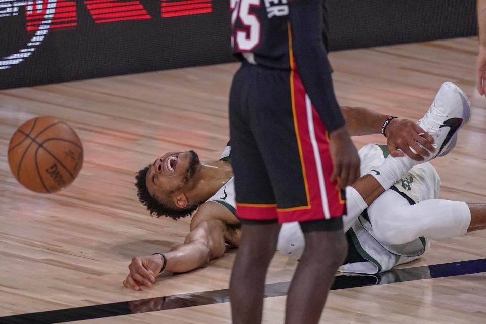 Milwaukee Bucks' Giannis Antetokounmpo reacts in pain on the basketball court.