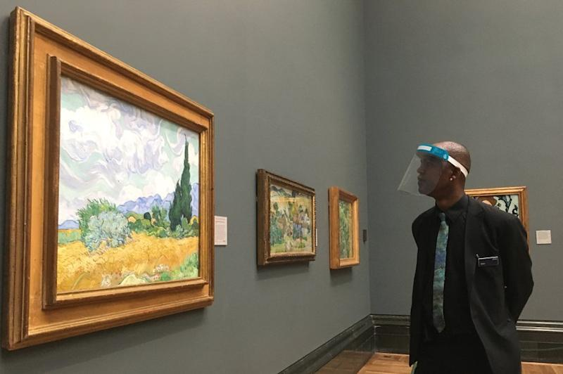 Visor-wearing member of National Gallery staff looking at A Wheatfield, with Cypresses, 1889, by Vincent van Gogh