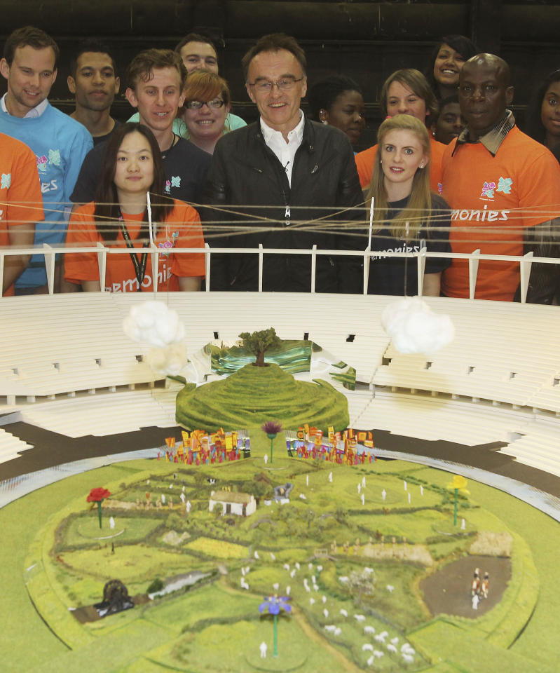 In this photo released Tuesday June 12, 2012 by the Olympic Organising Committee LOCOG, showing Danny Boyle, centre, with volunteers and a model of the rural English scene which will be the centre piece for the London 2012 Olympic Games Opening Ceremony.  With 45 days until the Opening Ceremony of the London 2012 Olympic Games artistic director of the ceremony Danny Boyle has unveiled the model and paid tribute to the 10,000 volunteers, cast and crew rehearsing night and day to make the Opening Ceremony a success.(AP Photo / Dave Poultney, Locog)