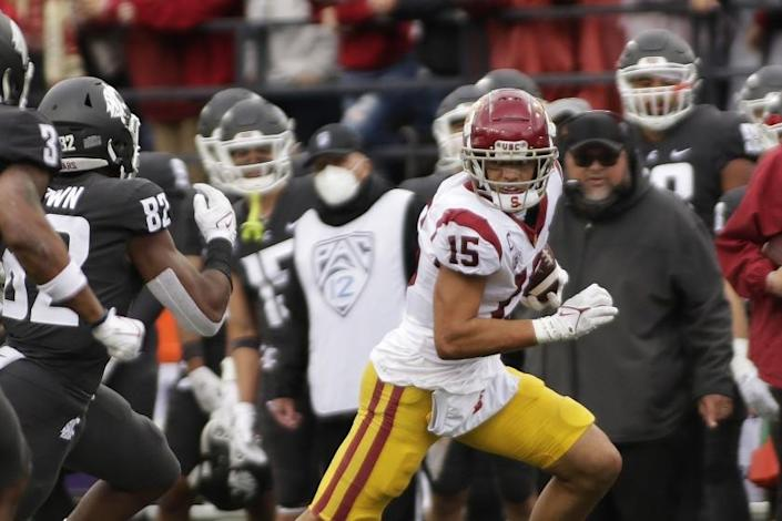 Southern California wide receiver Drake London (15) carries the ball while pursued by Washington State linebacker.
