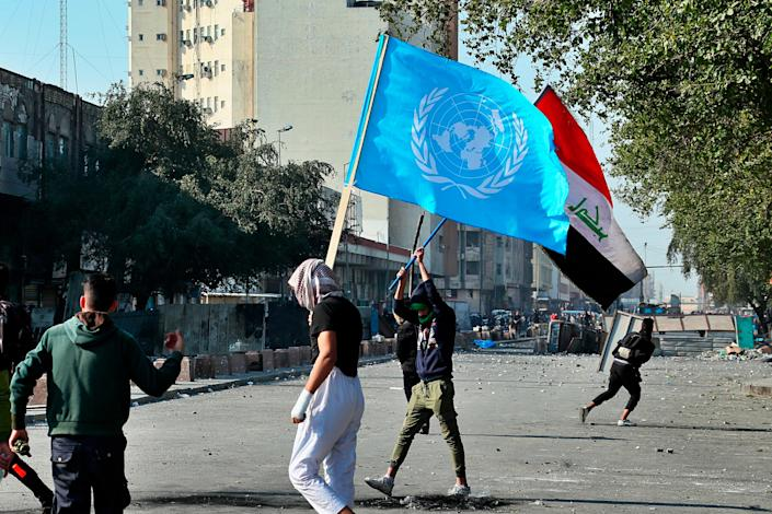 Anti-government protesters hold national and U.N. flags during clashes with security forces in Baghdad, Iraq, Friday, Jan. 31, 2020. (AP Photo/Hadi Mizban)