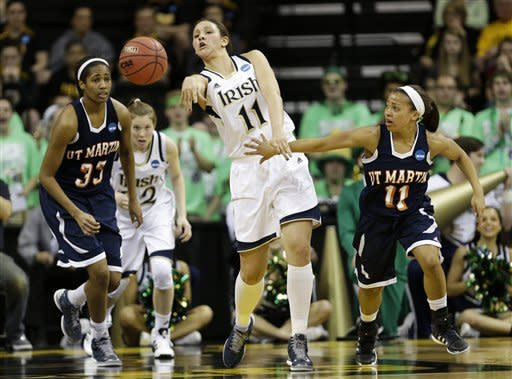 Notre Dame forward Natalie Achonwa, center, passes between Tennessee Martin forward Rickiesha Bryant, left, and guard Heather Butler, right, during the first half of a first-round game in the women's NCAA college basketball tournament on Sunday, March 24, 2013, in Iowa City, Iowa. (AP Photo/Charlie Neibergall)