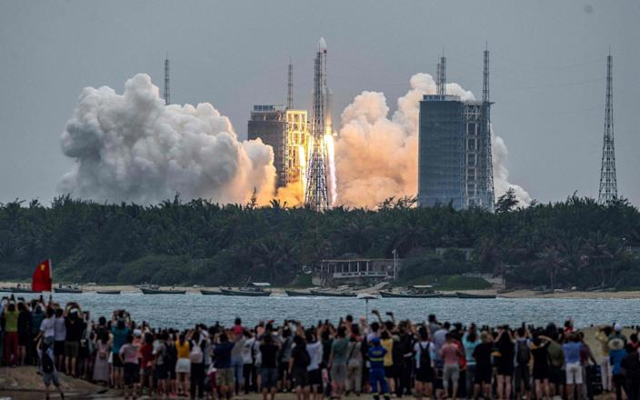 People watch a Long March 5B rocket, carrying China's Tianhe space station core module, as it lifts off from the Wenchang Space Launch Center in southern China's Hainan province - AFP