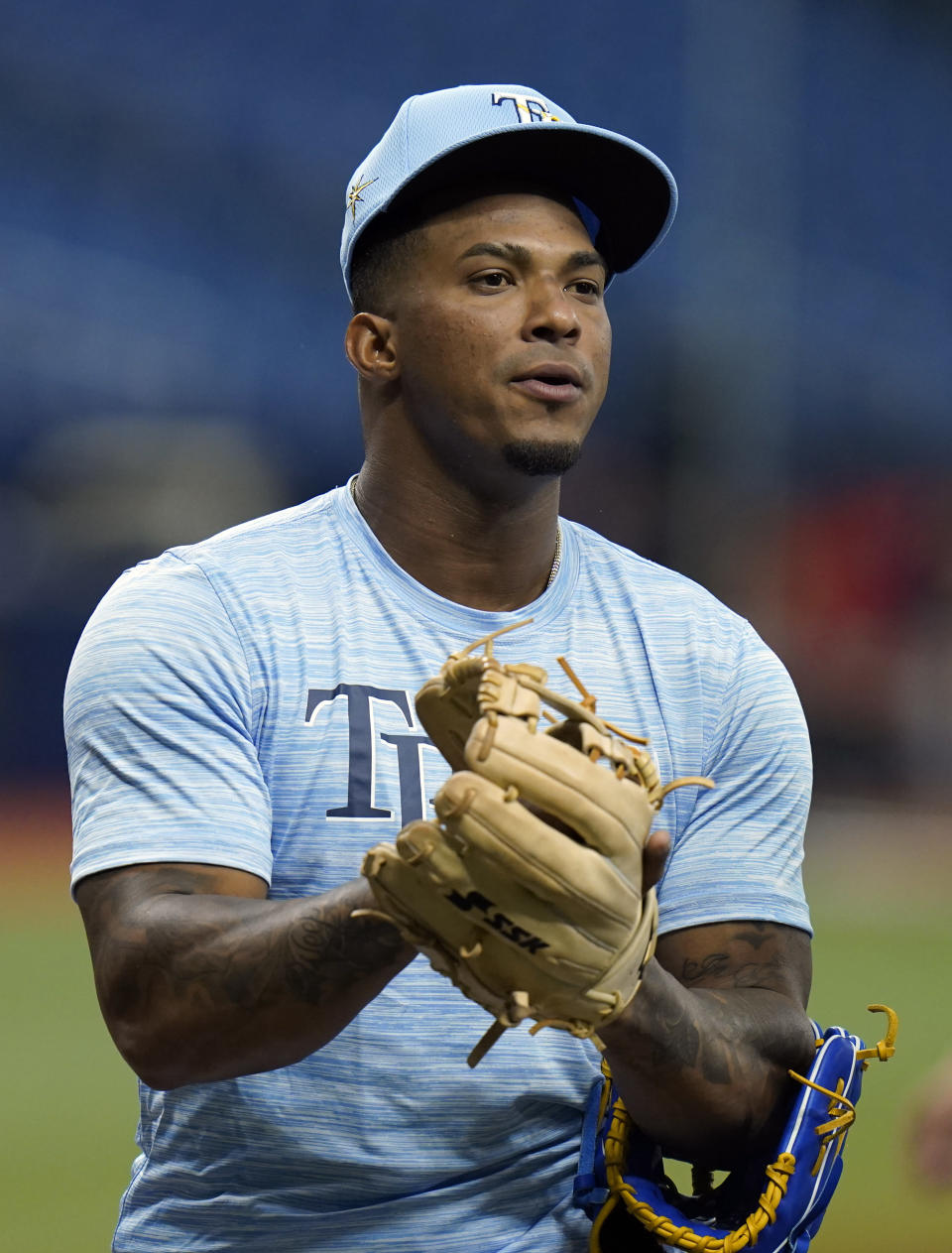 Tampa Bay Rays third baseman Wander Franco tries on gloves before a baseball game against the Boston Red Sox Tuesday, June 22, 2021, in St. Petersburg, Fla. The Rays called up Franco from their Class AAA Durham team. (AP Photo/Chris O'Meara)