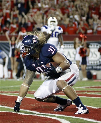 Arizona's Taimi Tutogi (31) tumbles into the end zone for a touchdown against South Carolina State during the first half of an NCAA college football game at Arizona Stadium in Tucson, Ariz., Saturday, Sept. 15, 2012. (AP Photo/Wily Low)