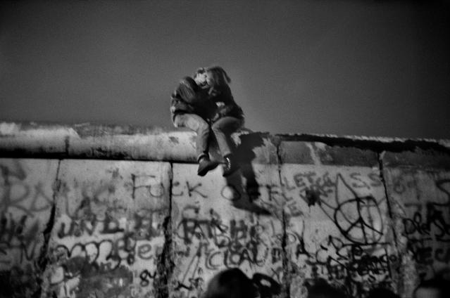 "<p>Berlin Wall, Sunday, Dec. 31, 1989. ""A few days after the fall of the Berlin Wall (the 9th of November, 1989), joy and enthusiasm were continuous. The euphoria grew even greater on New Year's Eve. A very dense human tide had gathered around the Brandenburg Gate: warmth, embraces here and there … In this incessant frenzy, tears blended with laughter. People of all ages, backgrounds and nationalities were becoming closer as the fireworks and squibs exploded relentlessly. Champagne was flowing.<br> After photographing the jubilation of this overexcited crowd, I decided to move to a quiet place. I glimpsed, hidden by a row of shrubs, a young couple sitting astride the top of the wall. They were surrendering to this intimate and peaceful moment to love each other and celebrate this new freedom."" (© Guy Le Querrec/Magnum Photos) </p>"