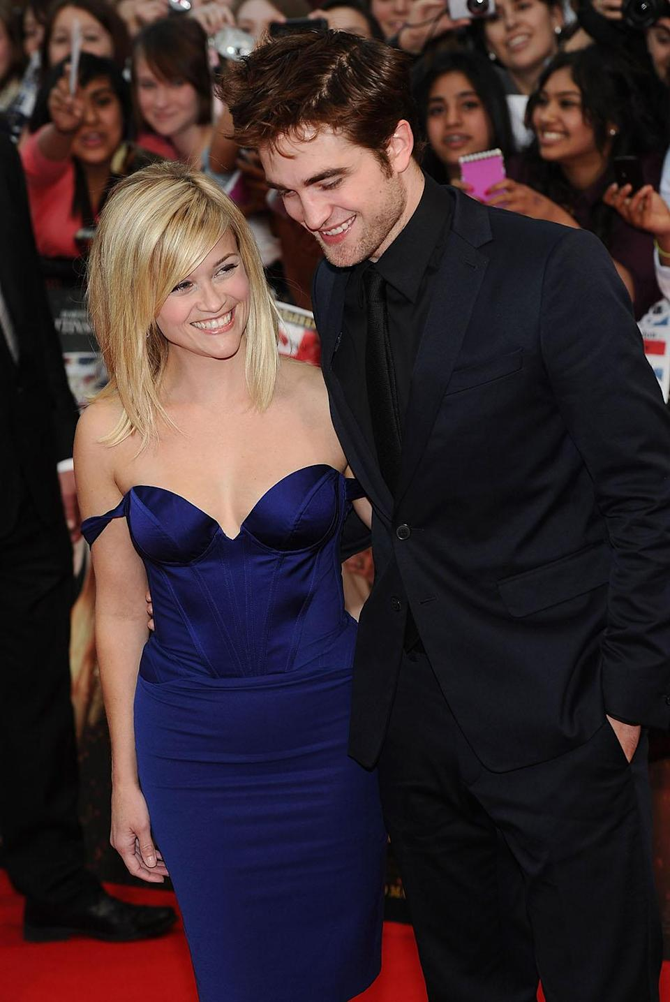 <p>Reunited with former <em>Vanity Fair</em> co-star and on-screen son, Reese shared a laugh with Robert Pattinson as they walked the red carpet at the London premiere of the film based on the 2006 novel. (Photo: Getty Images) </p>